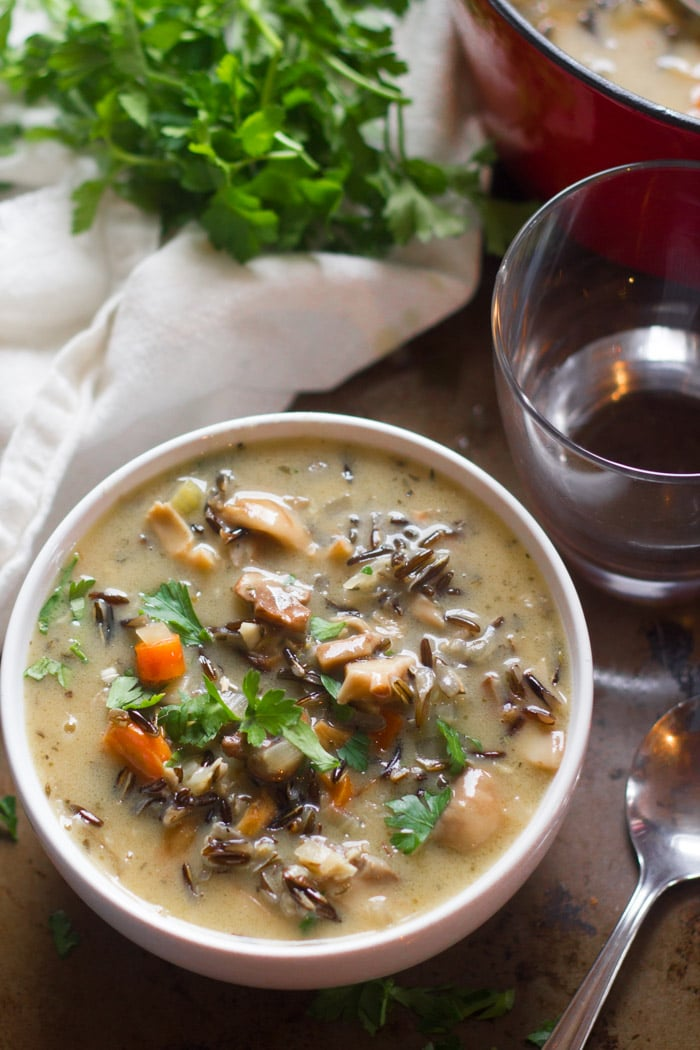 Creamy Mushroom Wild Rice Soup in a Bowl with Water Glass and Spoon