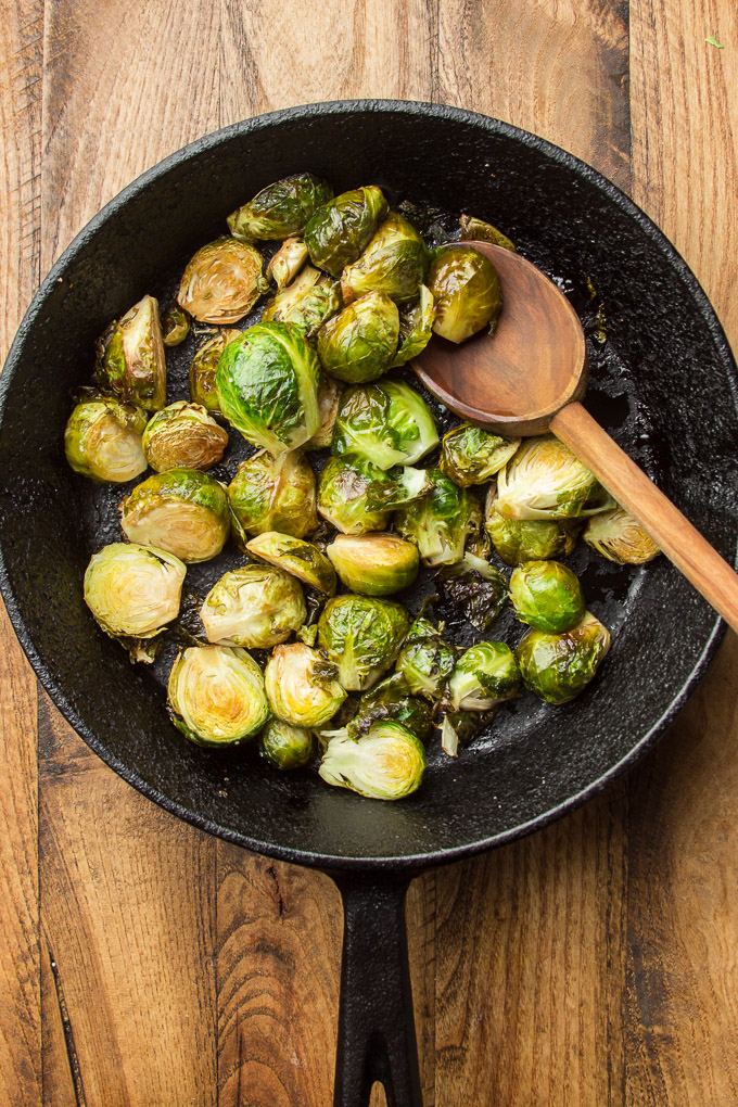 Cast Iron Skillet of Roasted Brussels Sprouts on a Wooden Table