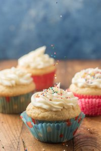 Sprinkles Being Dropped onto a Frosting-Topped Vegan Vanilla Cupcake