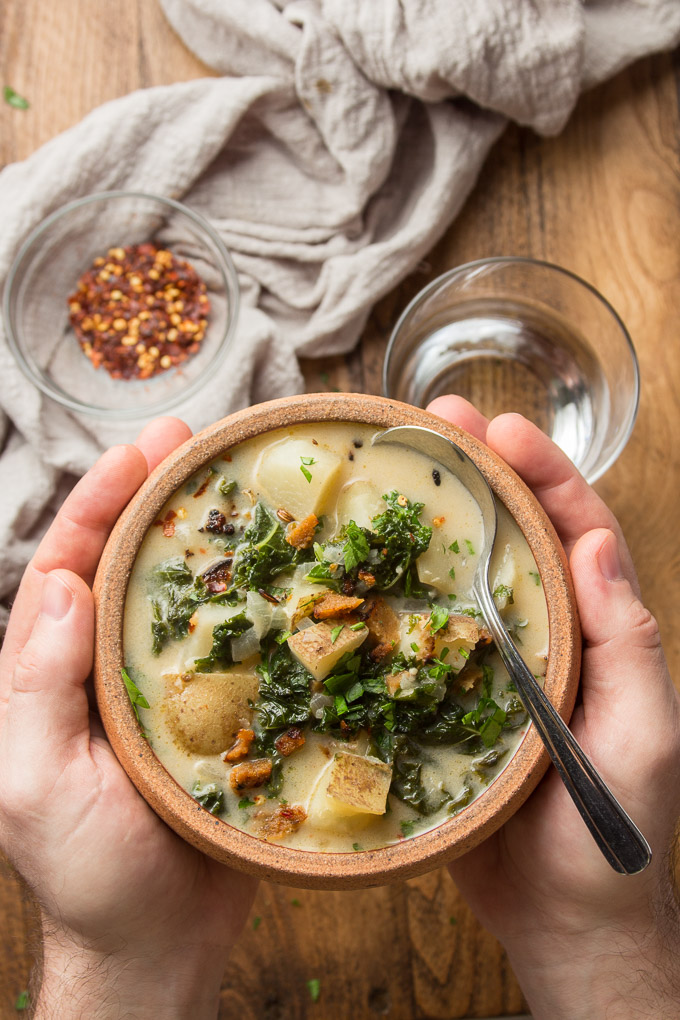 Pair of Hands Holding a Bowl of Vegan Zuppa Toscana Over a Wooden Table