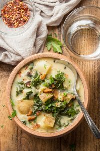 Vegan Zuppa Toscana in a Clay Bowl with Spoon, Water Glass and Bowl of Red Pepper Flakes