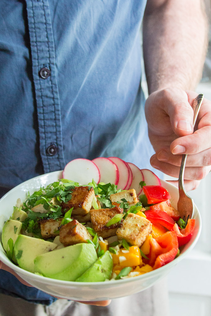 Hand Placing a Fork into a Vegan Poke Bowl