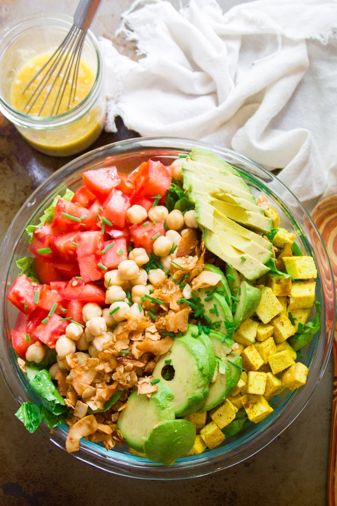 Overhead View of a Vegan Cobb Salad in a Serving Bowl with Napkin, Wooden Spoon and Dressing in a Jar