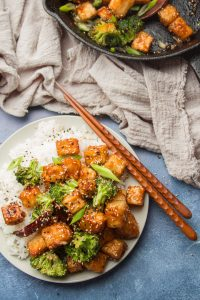 Plate of General Tso's Tofu, Chopsticks, Tea Towel and Cast Iron Skillet on a Blue Background