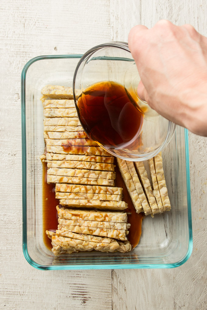 Hand Pouring Marinade Over Tempeh in a Glass Dish
