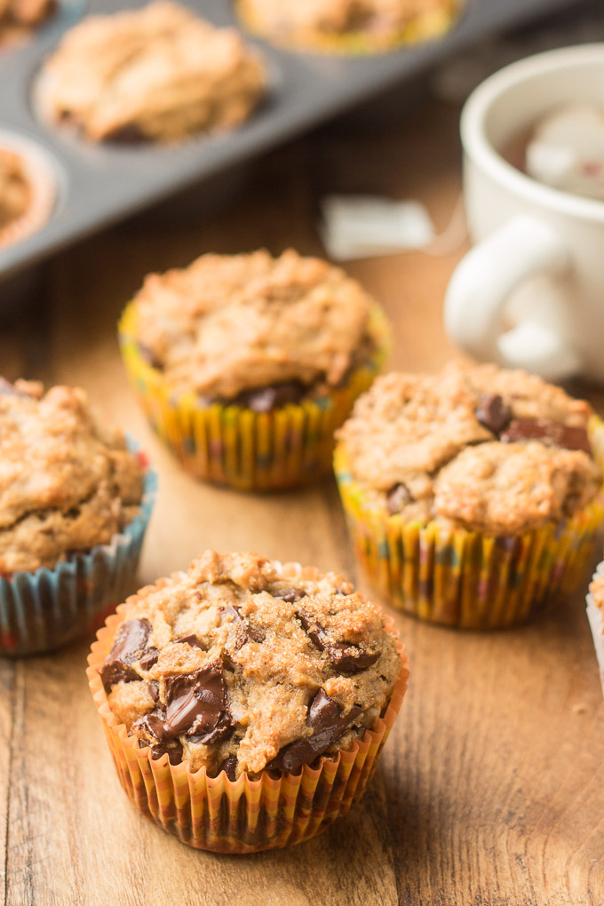 Vegan Banana Muffins on a Wood Table with Teacup in the Background