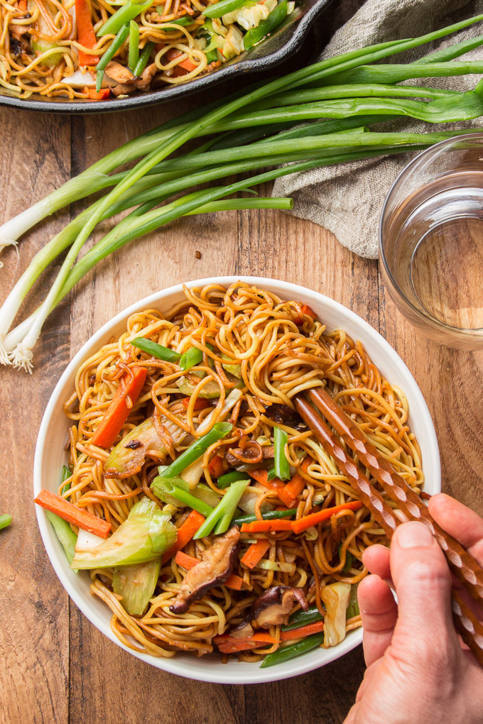 Hand Using Chopsticks to Grab a Bunch of Noodles from a Bowl of Vegetable Chow Mein