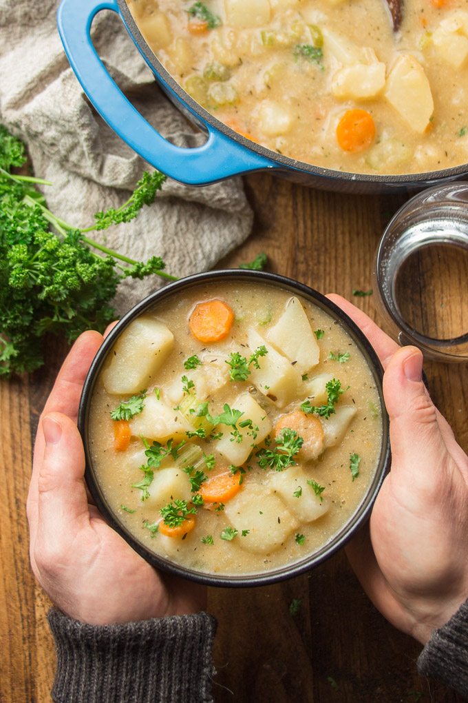 Pair of Hands Holding a Bowl of Vegan Potato Soup Over a Table