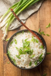 Bowl of Coconut Rice with Serving Spoon and Scallions
