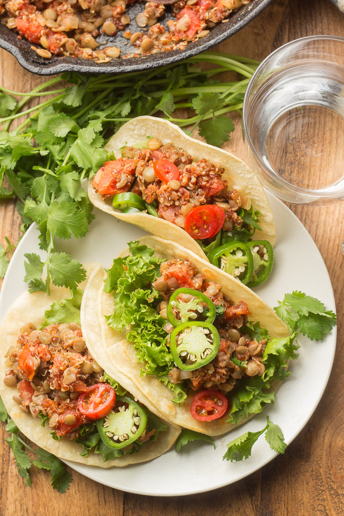 Wooden Table Set with a Plate of Lentil Quinoa Tacos, Skillet and Water Glass