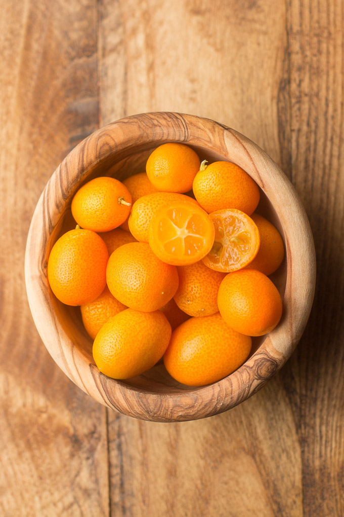 Bowl of Kumquats on a Wooden Surface