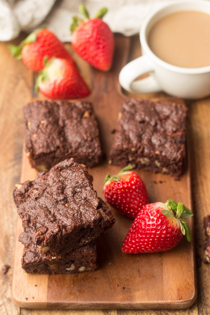 Vegan Brownies Arranged on Wooden Surface with Coffee Cup, and Strawberries