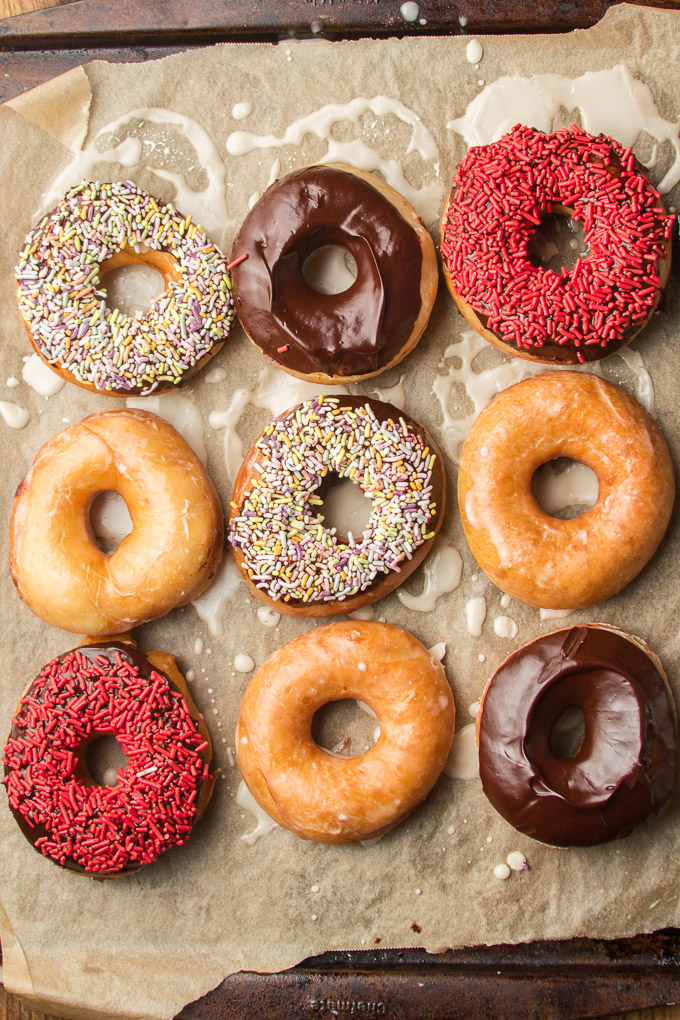 Nine Vegan Doughnuts on a Paper-Lined Baking Sheet