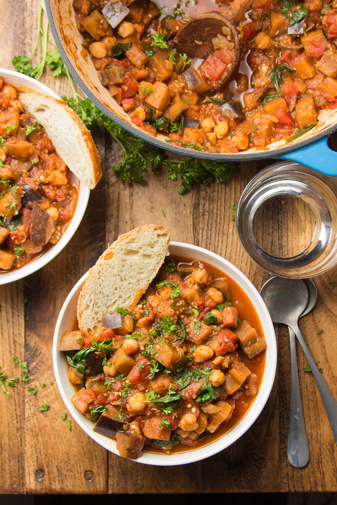 Two Bowls of Eggplant Stew with Bread Slices and Parsley on Top