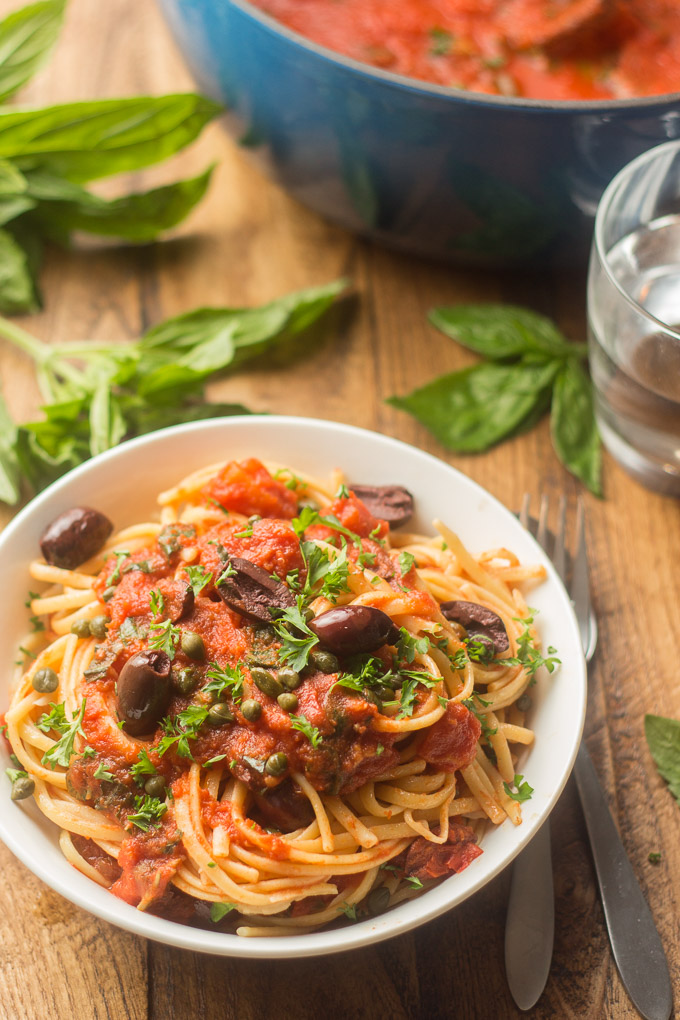 Bowl of Vegan Pasta Puttanesca with Water Glass and Basil Leaves in the Background