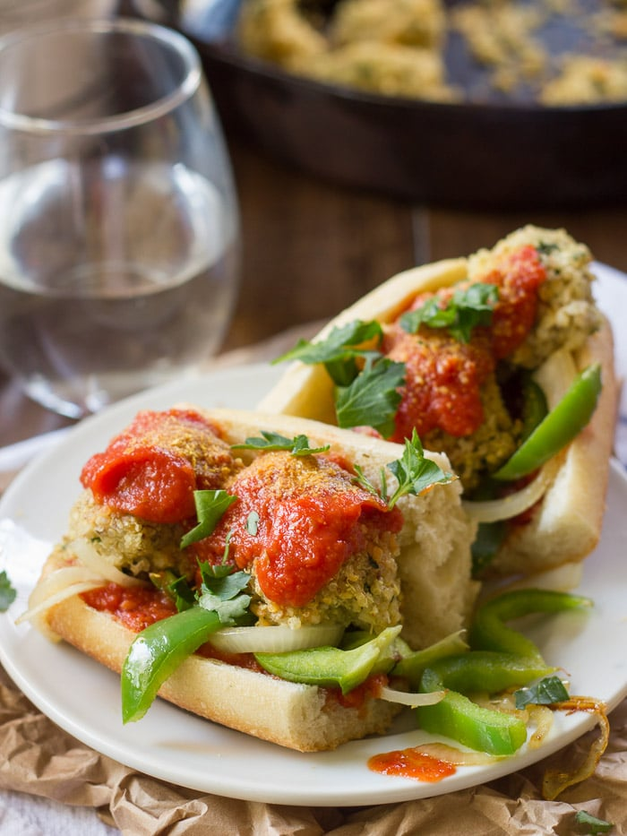 Two Halves of a Quinoa Meatball Sub on a Plate with Water Glass in the Background