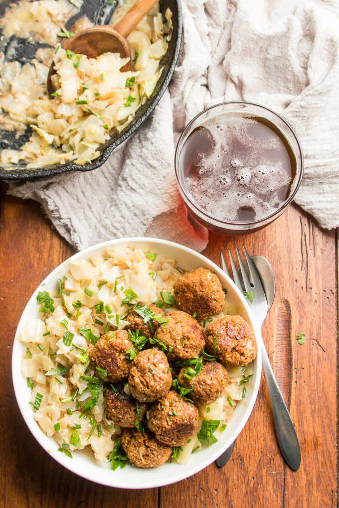 Table Set with Bowl of Vegan German Meatballs & Cabbage, Silverware, Napkin, Glass of Beer and a Skillet of Cabbage