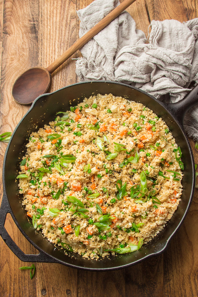Skillet of Cauliflower Fried Rice with Spoon on a Wooden Surface
