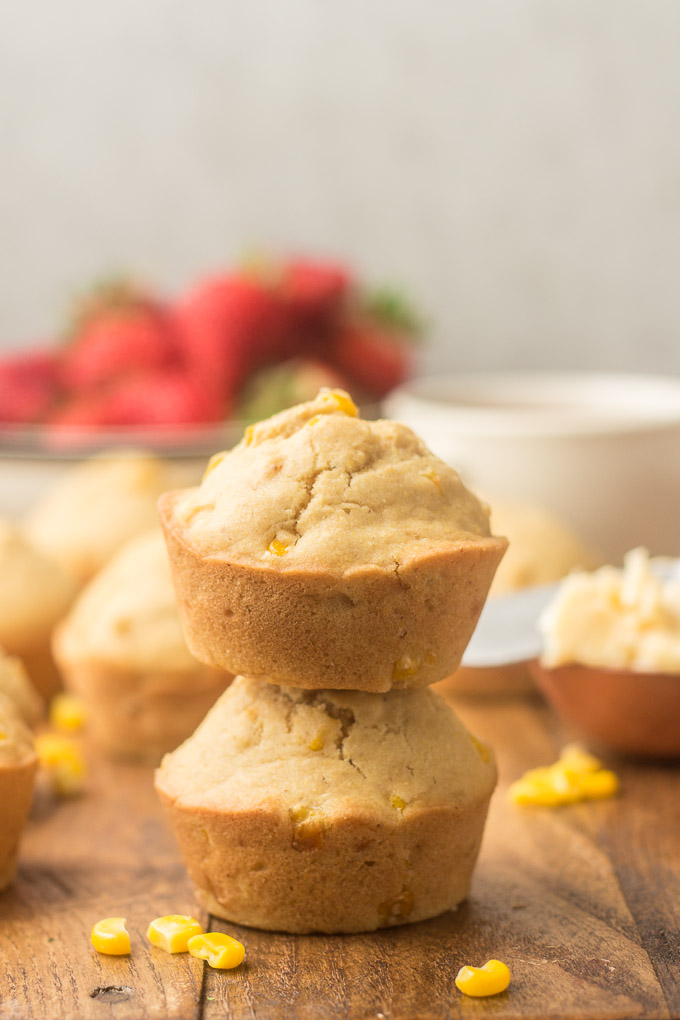 Two Stacked Vegan Corn Muffins with Strawberries, Muffins and Tea Cup in the Background