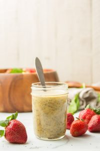 Jar of Poppy Seed Dressing with Strawberries and Wooden Salad Bowl in the Background