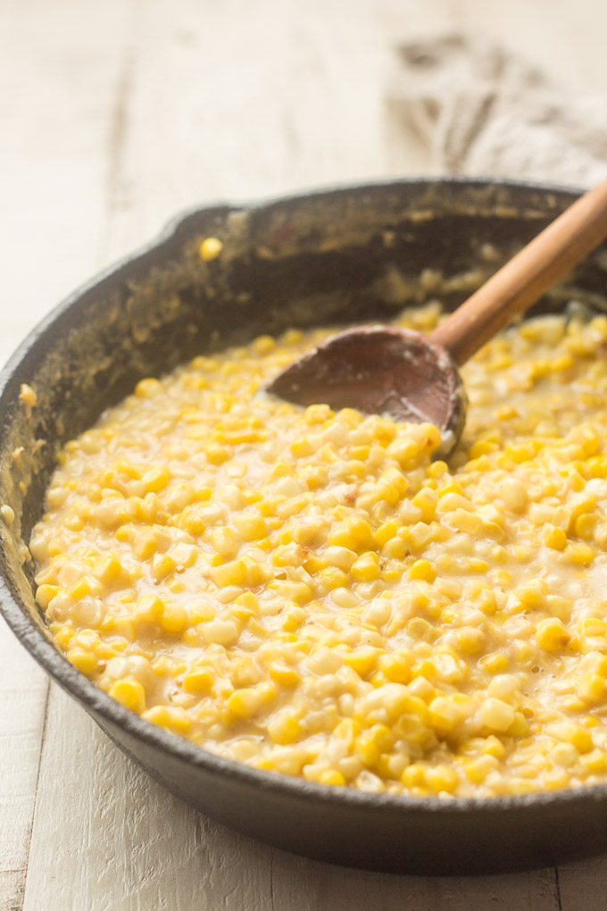 Vegan Creamed Corn in a Cast Iron Skillet with Wooden Spoon