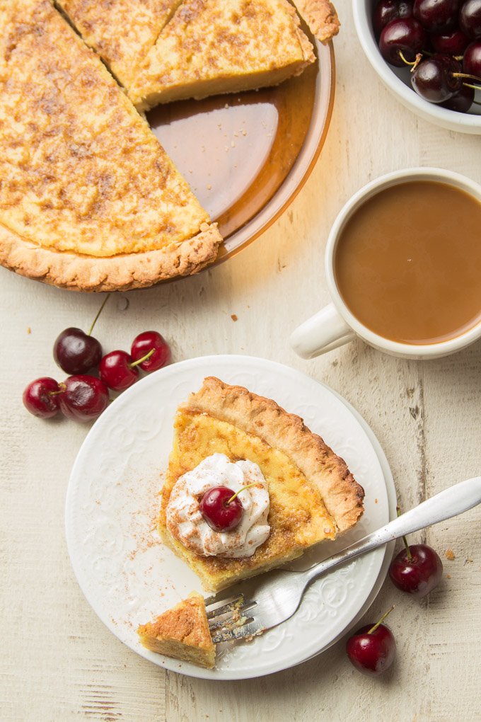 Overhead View of a White Table Set with Pie Plate, Bowl of Cherries, Coffee Cup, and Slice of Vegan Custard Pie with Whipped Topping an Cherry