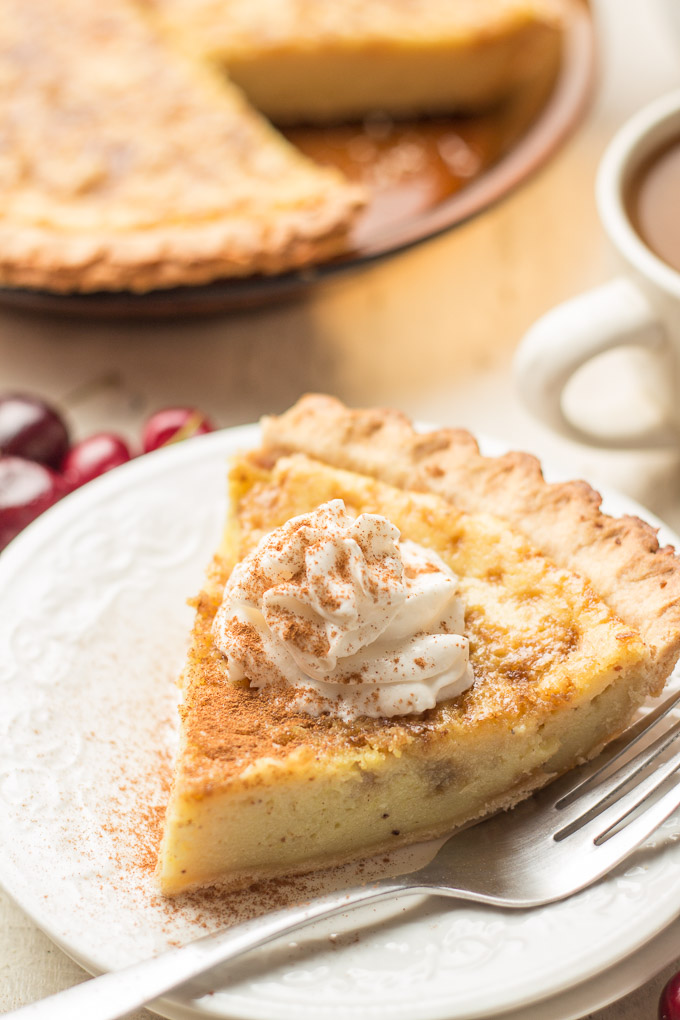 Slice of Vegan Custard Pie on a Plate with Pie Plate, Cherries, and Coffee Cup in the Background