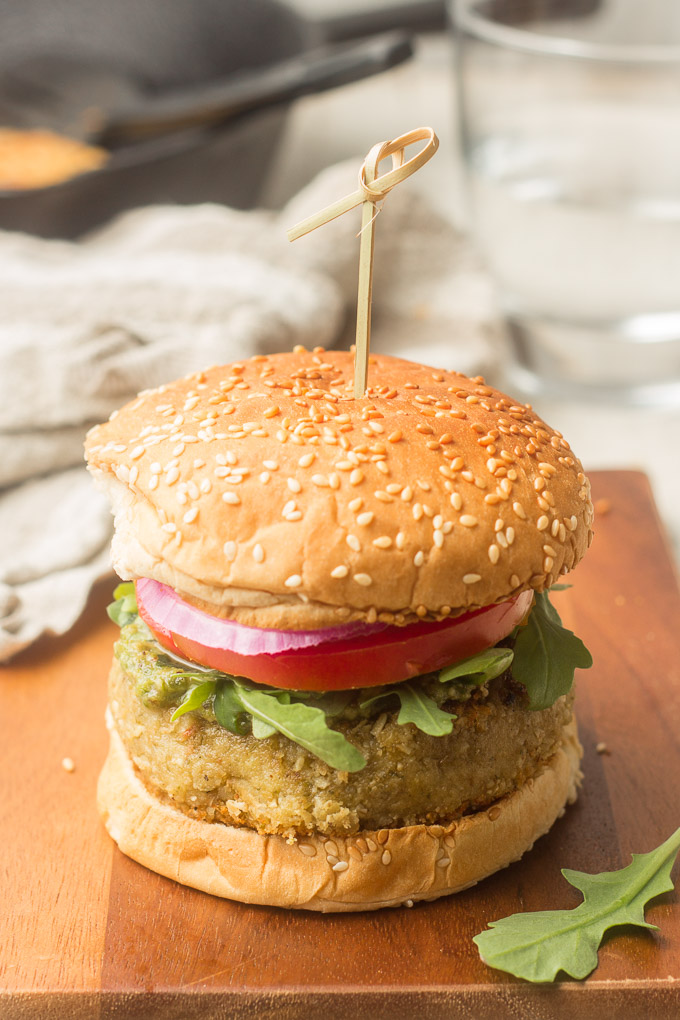 Pesto White Bean Burger on a Cutting Board with Water Glass and Skillet in the Background
