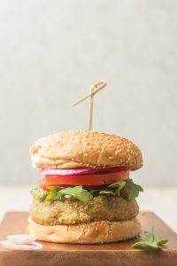 Pesto White Bean Burger on a Wooden Surface Against a Grey Background