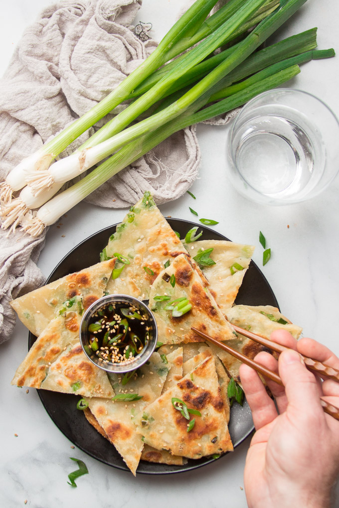Hand With Chopsticks Removing a Scallion Pancake Slice from a Plate