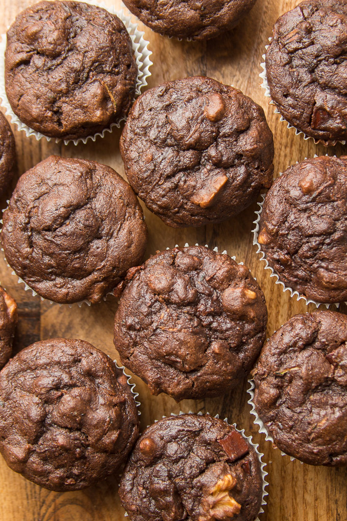 Vegan Chocolate Zucchini Muffins Lined Up on a Wooden Surface