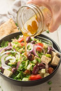 Hand Pouring Dressing Over Vegan Greek Salad in a Serving Bowl