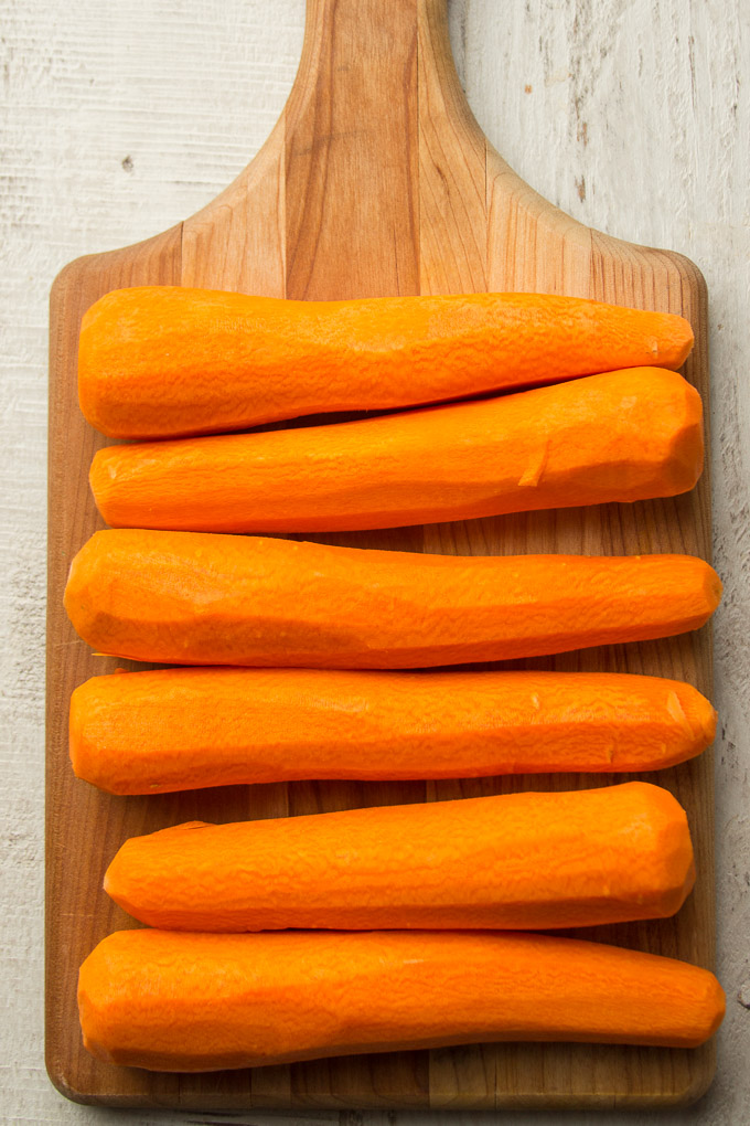 Six Peeled Carrots on a Cutting Board