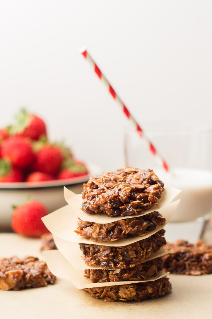 Stack of 5 Vegan No-Bake Cookies with Bowl of Strawberries and Glass of Almond Milk in the Background