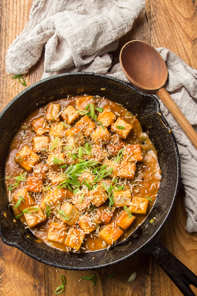 Skillet of Sweet & Sticky Coconut Tofu with Wooden Spoon on the Side
