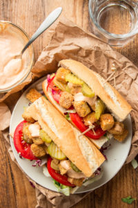 Overhead View of Two Halves of a Vegan 'Po Boy Sandwich on a Plate with Remoulade Sauce on the Side