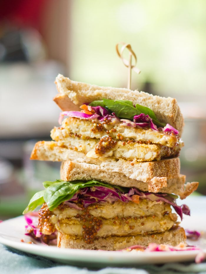Two Halves of a Crispy Tempeh Sandwich Stacked on a Plate