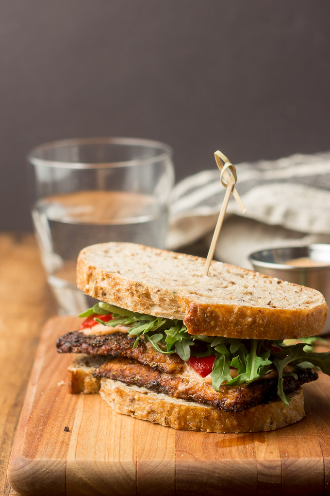 Blackened Tempeh Sandwich on a Cutting Board with Glass of Water in the Background