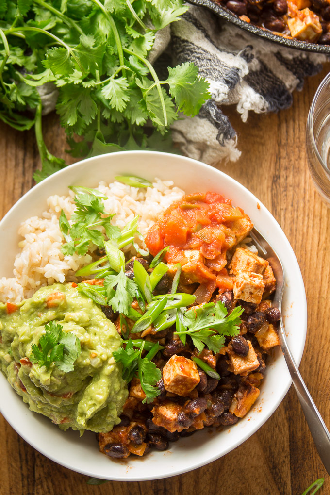Tofu and Black Bean Burrito Bowl Topped with Salsa and Guacamole on a Wooden Surface
