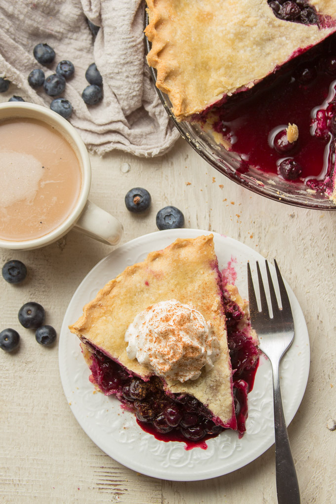Overhead View of a Table Set with Vegan Blueberry Pie, Slice of Pie on a Plate, Fork, and Coffee Cup