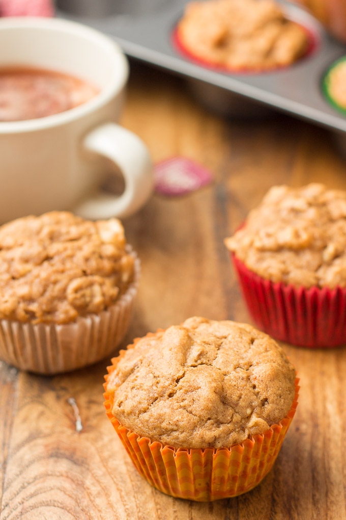 Three Vegan Apple Cider Muffins on a Wooden Surface with Tea Cup and Muffin Tin in the Background