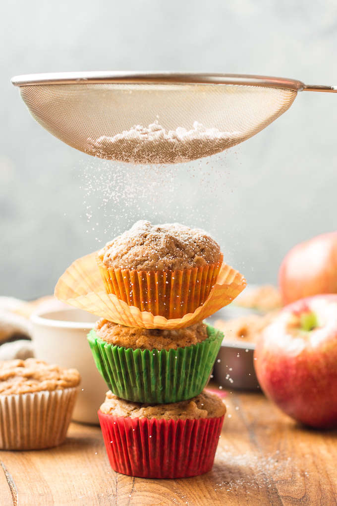 Sifter Sifting Powdered Sugar Over a Stack of Three Vegan Apple Cider Muffins