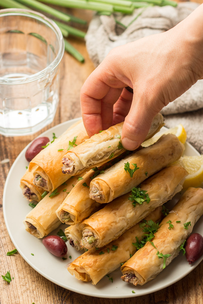 Hand Grabbing a Phyllo Cigar from a Plate