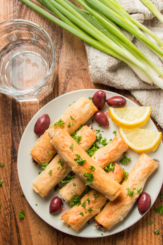 Wooden Table Set with a Plate of Phyllo Cigars, Lemon Wedges and Olives, Water Glass, and Bunch of Scallions