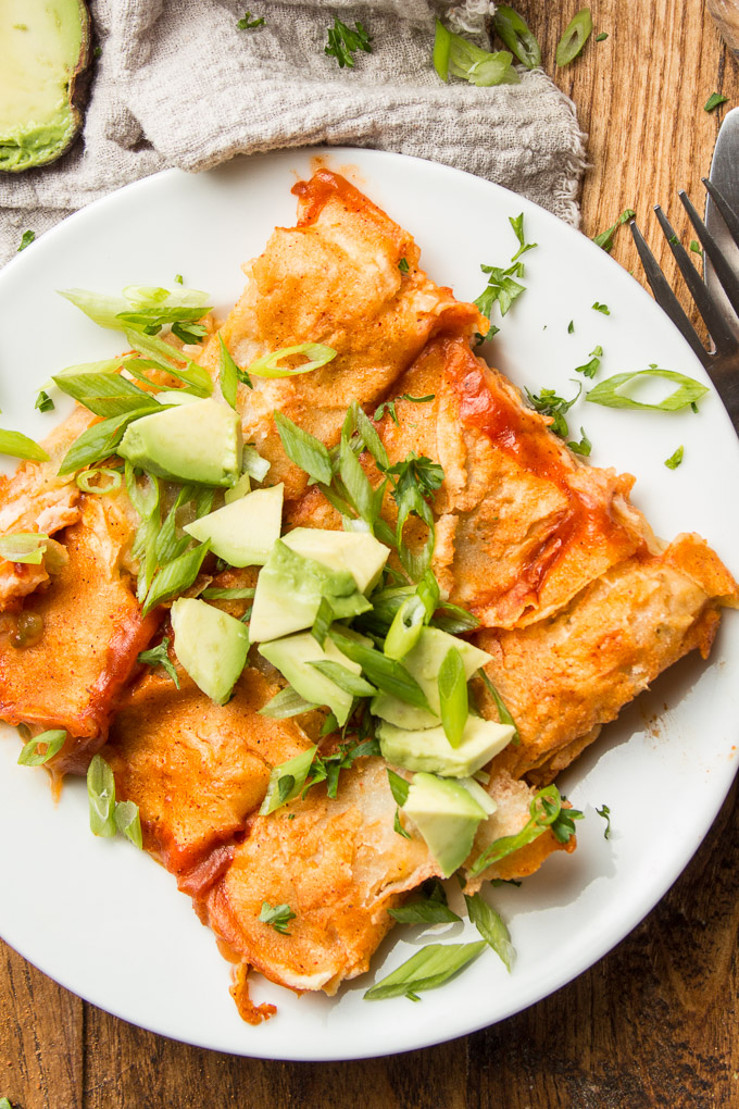 Three Mashed Potato Enchiladas on a Plate Topped with Scallions and Avocado