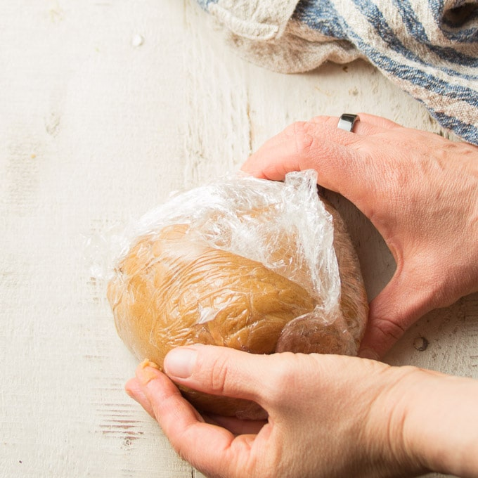 Hands Wrapping a Ball of Vegan Peanut Butter Cookie Dough in Plastic