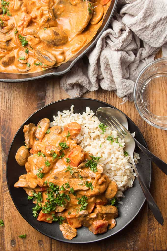Wooden Table Set with Skillet, Water Glass, and Plate of Vegan Mushroom Paprikash with Rice