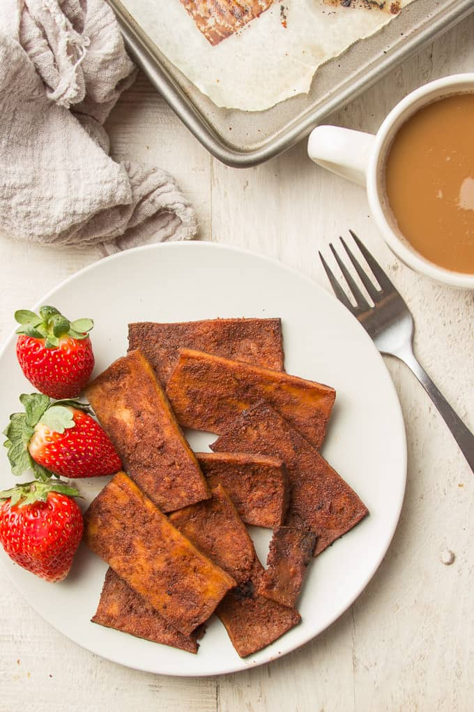 White Wooden Surface Set with Coffee Cup, Baking Sheet and Plate of Tofu Bacon and Strawberries