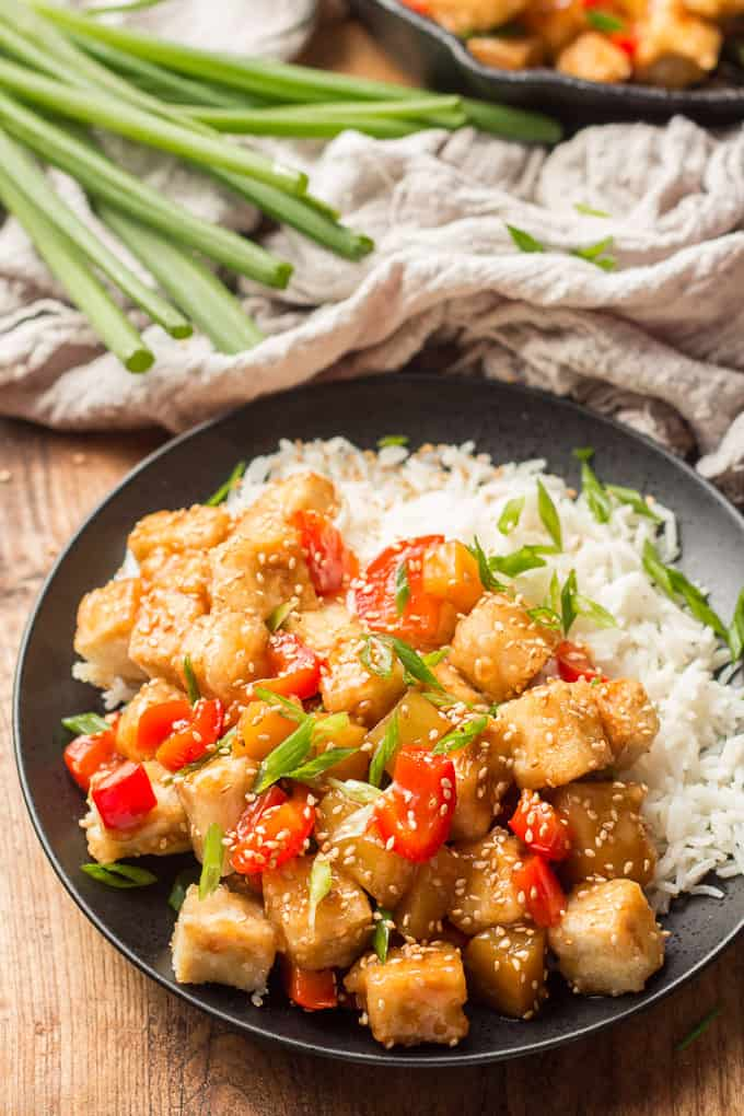 Plate of Sweet & Sour Tofu and Rice with Skillet and Bunch of Scallions in the Background