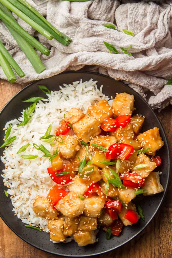 Plate of Sweet & Sour Tofu and Rice with Fabric and Bunch of Scallions on the Side